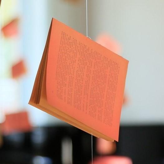Ein rosa angemaltes Buch hängt an einer Schnur von der Decke.