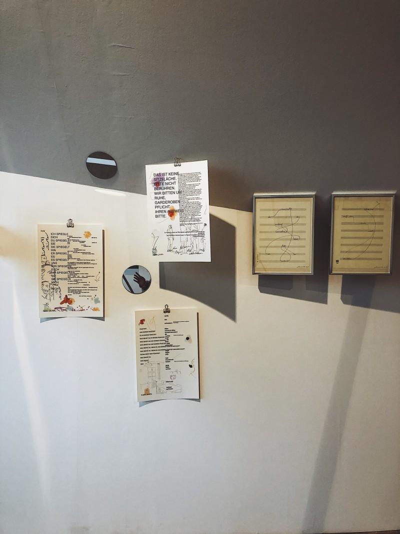 Fünf Text und Illustrationsbildern an einer Wand hängend. Daneben zwei kleine runde Spiegel.