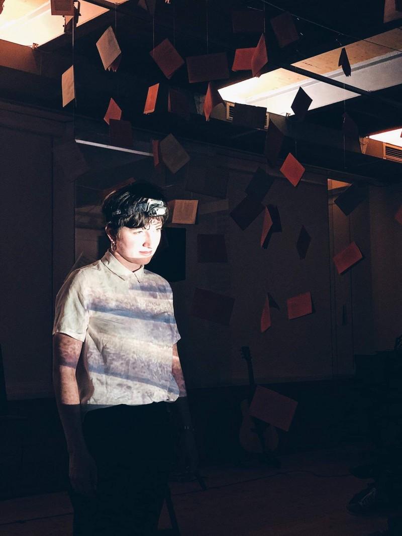 Eine Schauspielerin steht in einem dunklen Raum und wird von einem hellen Licht angestrahlt.