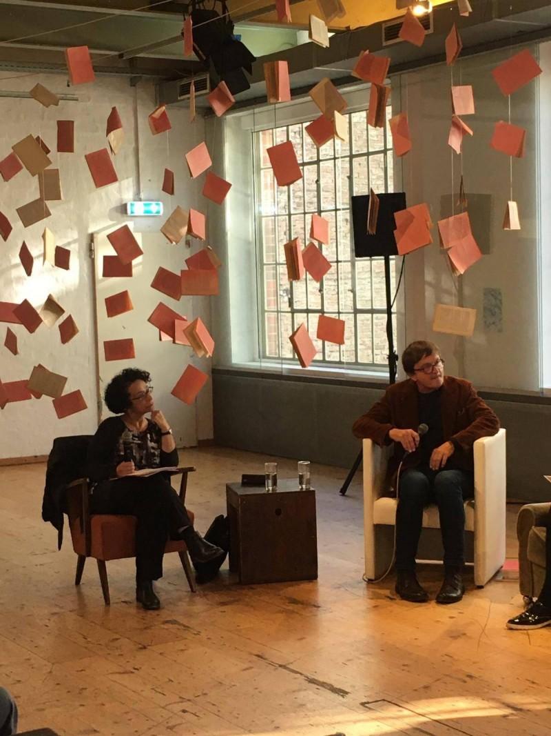 Zwei Menschen sitzen auf Sesseln im Brick-5 und hören aufmerksam zu.
