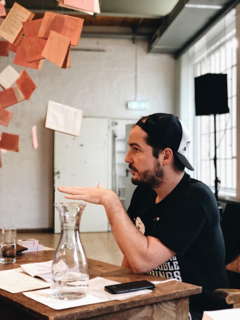 Max Czollek sitzt an einem Tisch und redet.