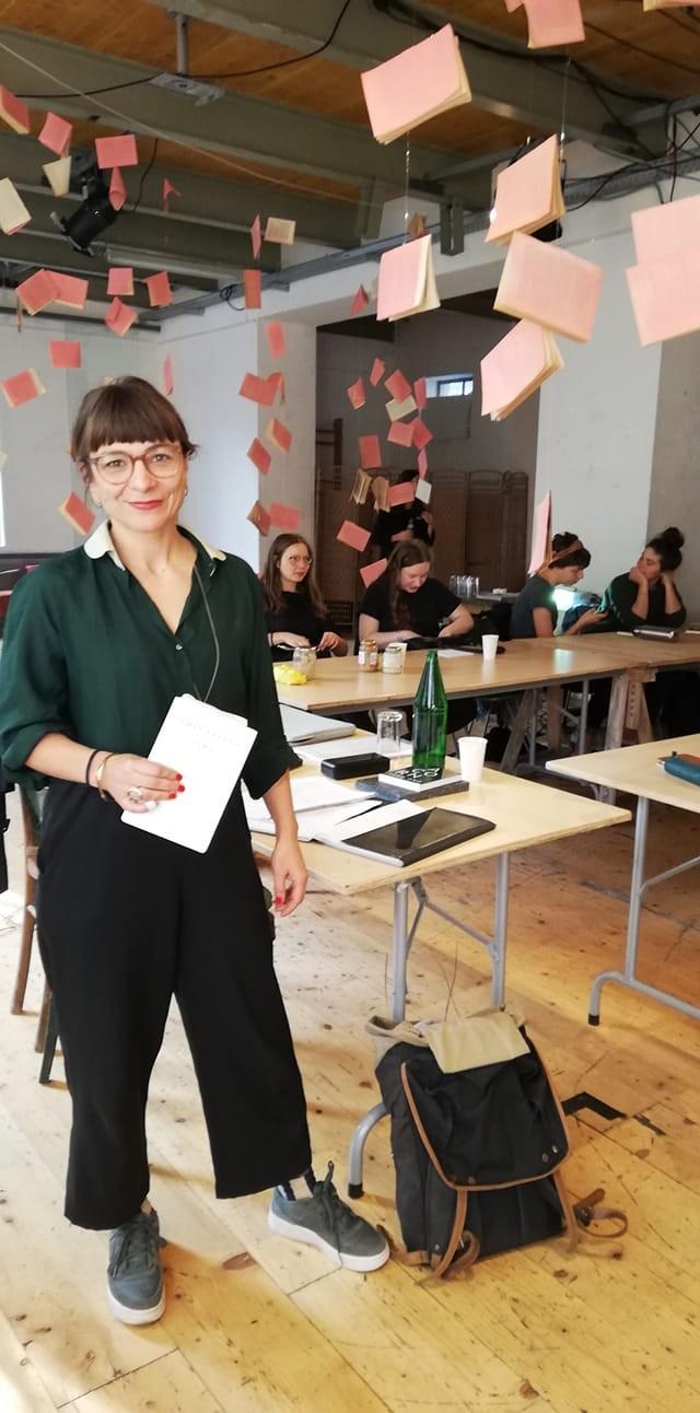 Uljana Wolf steht lächelnd und hält ein Papier in der Hand.