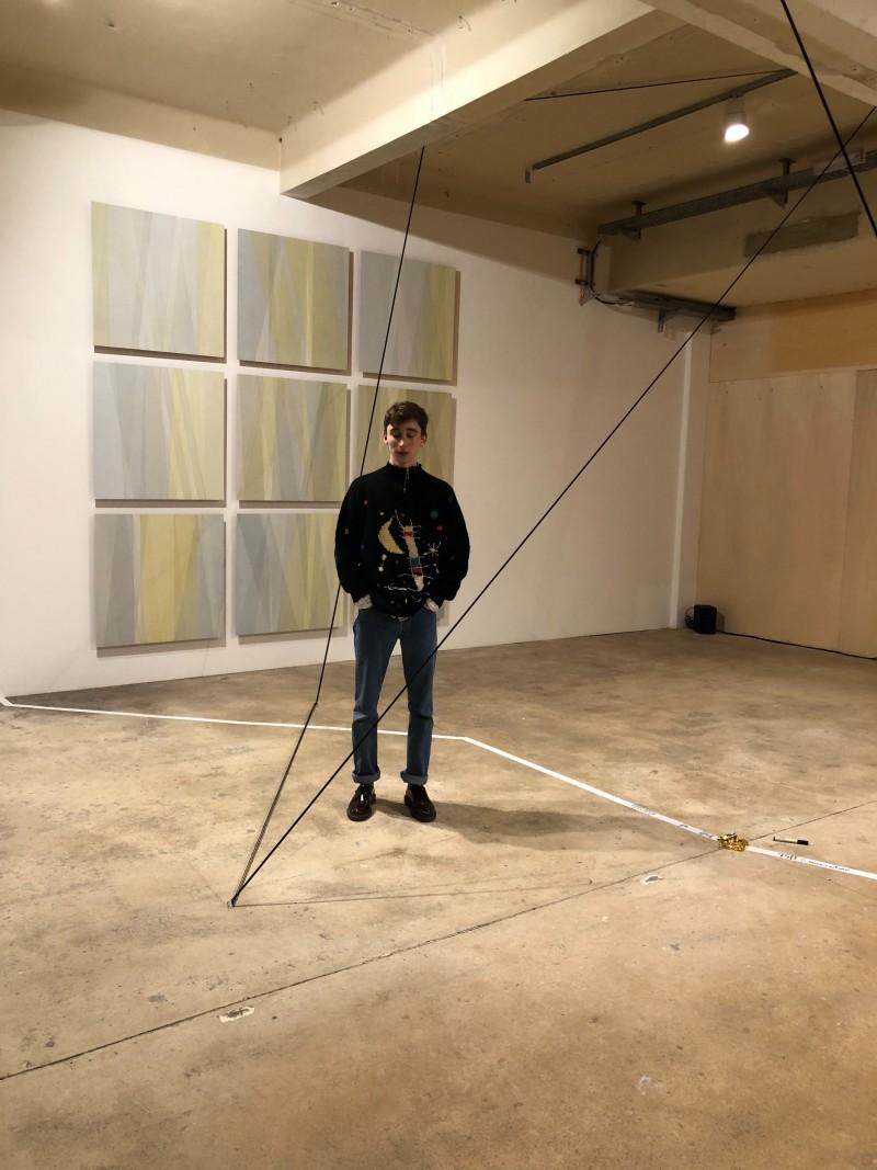Felix steht in einem Raum des Künstlerhaus 1050, im Hintergrund Malereien.