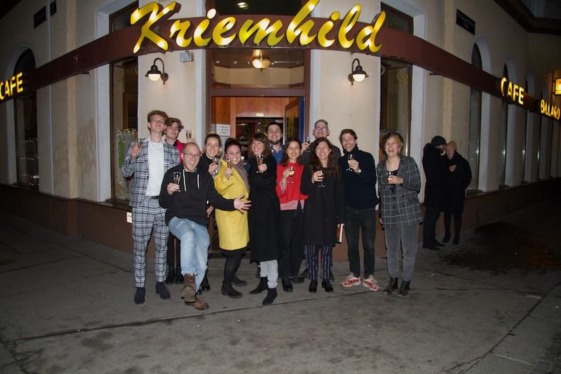 Eine Gruppe Studierender steht vor dem Cafe Kriemhild und lächelt und hält ihre Gläser hoch.