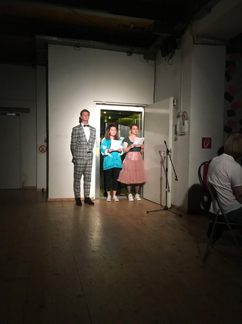 Drei Schauspieler*innen stehen im Spotlight und lesen Texte vor.